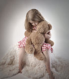 Sad Little Girl Holding Teddy Bear. A sad little girl is holding a stuffed teddy bear on an isolated background for a timeout or emotion concept stock images