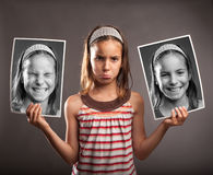 Sad little girl holding two photos of herself Stock Photos