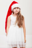 Sad little girl kid in santa claus hat. Christmas. Stock Image
