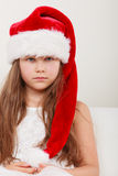 Sad little girl kid in santa claus hat. Christmas. Stock Images