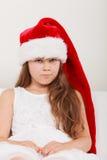Sad little girl kid in santa claus hat. Christmas. Royalty Free Stock Photos