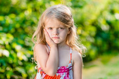 Sad little girl with long blond hair suffering from toothache stock photography