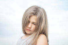 A sad little girl looking down. A background of blue sky royalty free stock photography