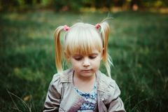 Sad little girl looking down, showing emotions. In summer outdoors Royalty Free Stock Photo