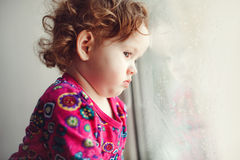 Sad little girl. Looking out the window Royalty Free Stock Image