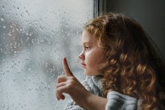 Sad little girl looking out the window on rain drops near wet gl Royalty Free Stock Images