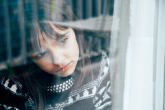Sad little girl. Looking through the window with reflections on her face Royalty Free Stock Photo