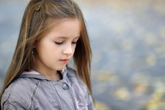 Sad little girl looks aside in autumn in the park Stock Images