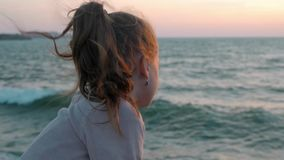Sad little girl looks at the ocean sitting on jetty on beach during storm windy day. slow motion.  stock video