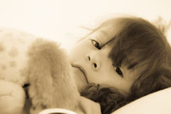 Sad little girl lying in bed in the bedclothes. colortoned Royalty Free Stock Photo