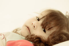 Sad little girl lying in bed colortoned Royalty Free Stock Photos