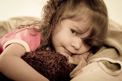 Sad little girl lying in bed colortoned Stock Photos