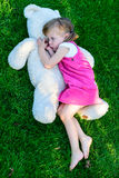 Sad little girl lying on grass with large teddy bear Stock Photo