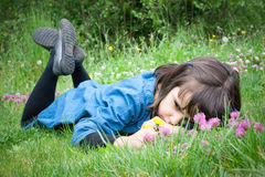 Sad little girl lying in the grass Royalty Free Stock Photos