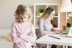Sad little girl not getting mother`s attention. Working mother concept stock photography