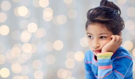 Sad little girl over holidays lights background Royalty Free Stock Image