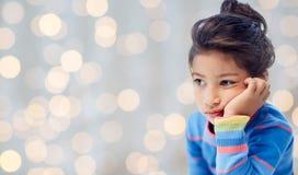 Sad little girl over holidays lights background Royalty Free Stock Image