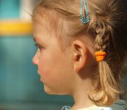Sad little girl with pigtail and a tear on her cheek stock photo