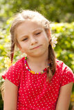 Sad little girl with pigtails. In a red blouse Stock Photos