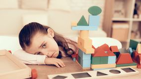 Sad Little Girl Playing with Kids Cubes at Home. Little Girl Playing Cubes. Educational Games. Learning Child at Home. Build House of Cubes. Child Development royalty free stock photo