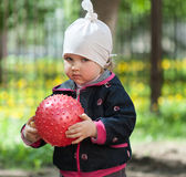 Sad little girl playing with a red ball Royalty Free Stock Photography