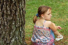 Sad Little Girl, Pouting. Lost Little girl pouting under tree Royalty Free Stock Photo