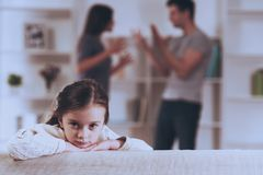 Sad Little Girl with Quarrel Parents. Child Suffering. Family at Home. Quarrels Upset Child. Young Parents. Angry Father. Aggresive Couple. Depressed Girl royalty free stock images