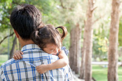 Sad little girl resting on her father's shoulder Royalty Free Stock Image