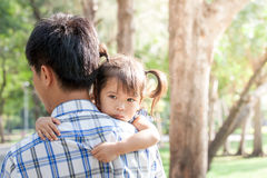 Sad little girl resting on her father's shoulder Royalty Free Stock Photo