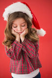 Sad little girl in santa hat. On red background Stock Photos