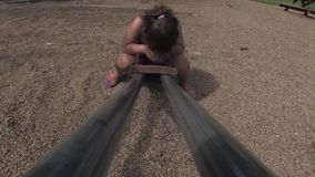 Sad Girl on See Saw. A sad little girl sits alone on a seesaw stock video