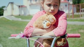 A sad little girl sits on a bike alone stock video footage
