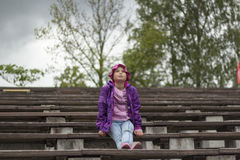 Sad little girl is sitting on the bench Stock Photography