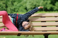 Sad little girl sitting on bench in the park at the day time stock photos