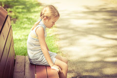 Sad little girl sitting on bench in the park. At the day time Royalty Free Stock Images