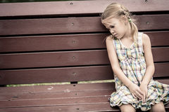 Sad little girl sitting on bench in the park Stock Photo