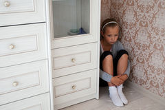 Sad little girl sitting in the corner of a room. Behind the cupboard Stock Photos