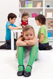 Sad little girl sitting excluded by friends Royalty Free Stock Photo