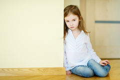 Sad little girl sitting on a floor Royalty Free Stock Images