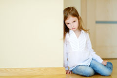 Sad little girl sitting on a floor Stock Images