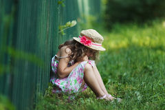 Sad little girl sitting on grass Stock Image