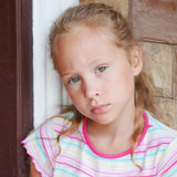 Sad little girl sitting near a door Royalty Free Stock Photo