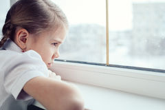 Sad little girl sitting near the window. One sad little girl sitting near the window at the day time. Concept of sorrow royalty free stock photos