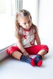 Sad little girl sitting near the window Stock Images