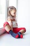 Sad little girl sitting near the window Royalty Free Stock Photography