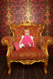 Sad little girl sitting in old armchair Stock Photo