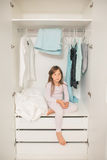 Sad little girl sitting in wardrobe. Alone sad little girl sitting in mother's wardrobe. Concept: problem to choose clothes for female Stock Images