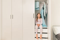 Sad little girl sitting in wardrobe Royalty Free Stock Photos