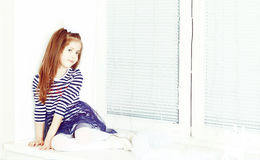 Sad little girl sitting by the window. Stock Images