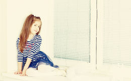 Sad little girl sitting by the window. Royalty Free Stock Photo
